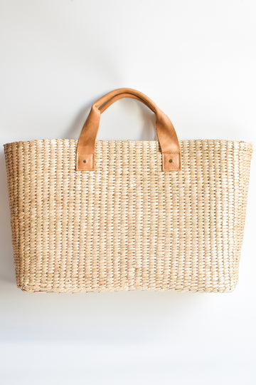 Large straw tote bag finished with natural leather handles and linen lining.