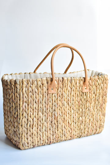 Extra large natural hyacinth straw tote with matching leather handles.