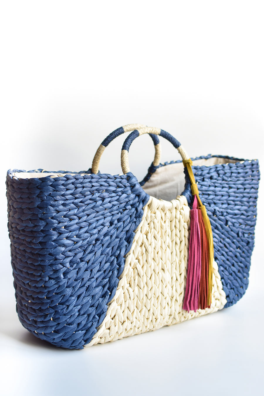 Navy and natural colored over-sized straw tote with circle handle and suede tassels.
