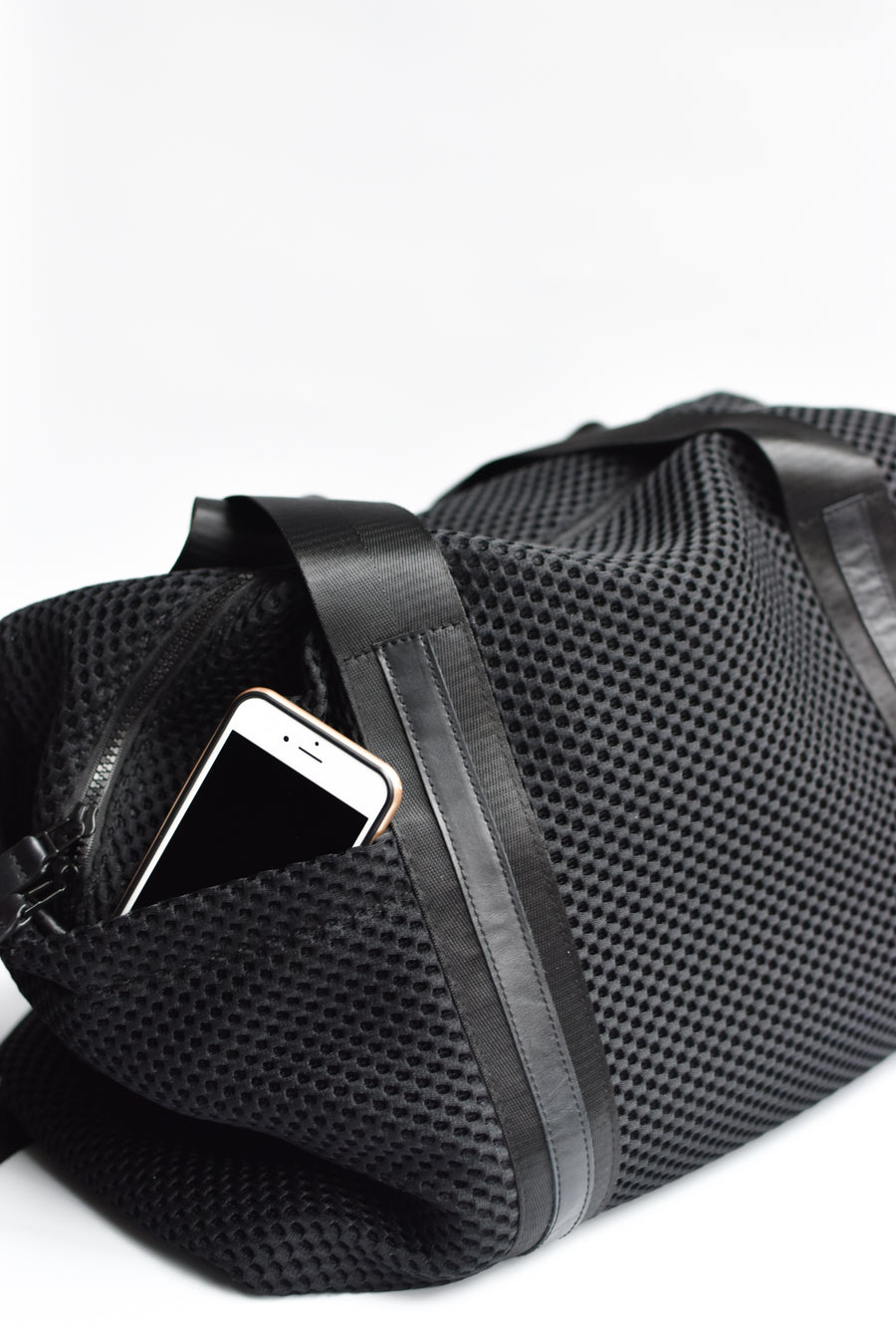 Close up of exterior side pocket on black mesh duffel bag with leather trim details.