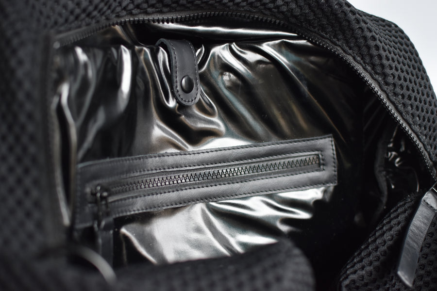 Close up of interior black glossy lining on black mesh duffel bag with leather trim details.