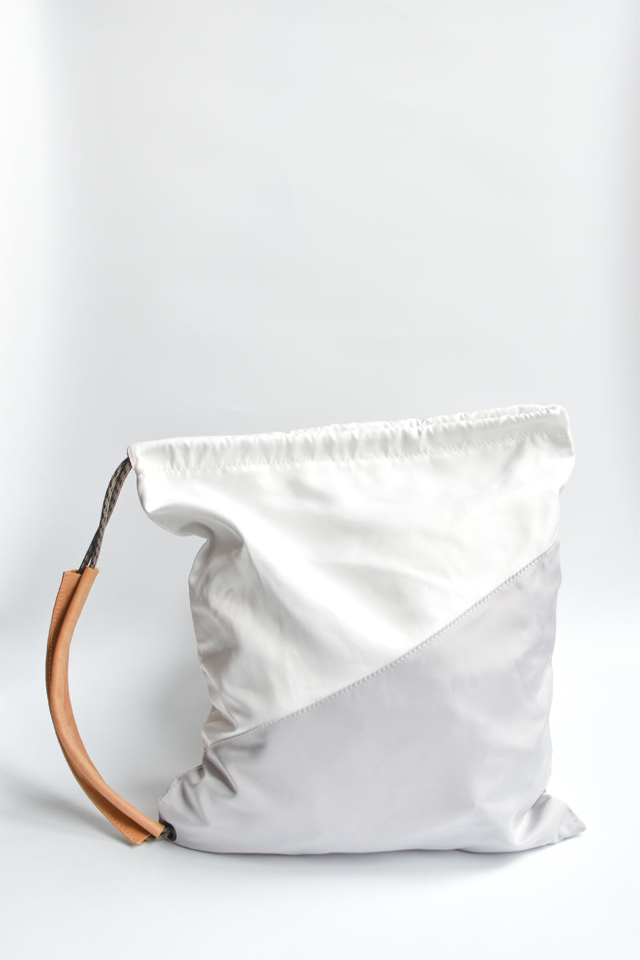 Sporty nylon sling bag in white and gray with natural leather straps.