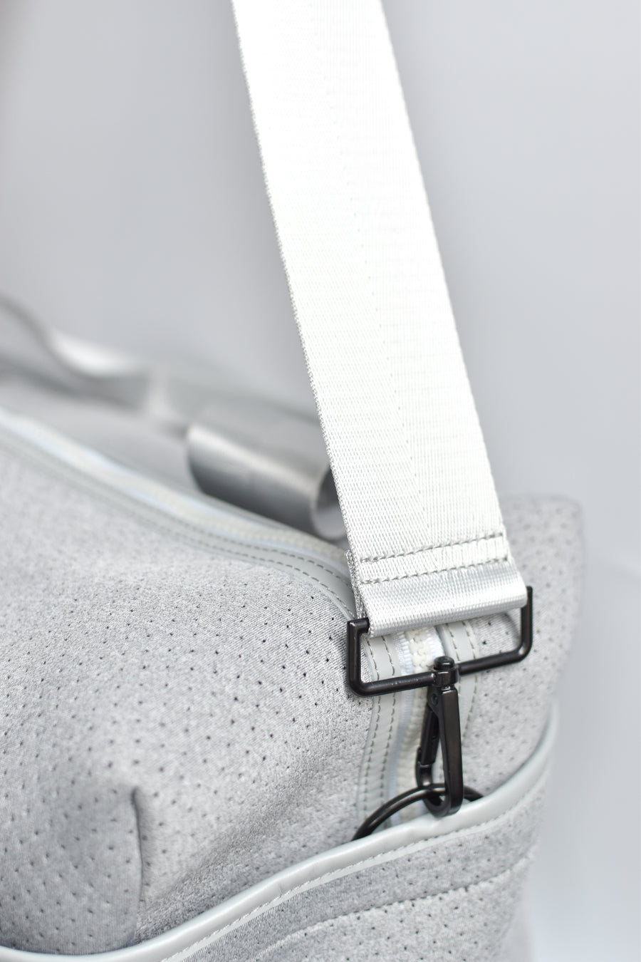 Close up of side pocket and cross-body strap on the Callahan light gray perforated neoprene duffel bag.