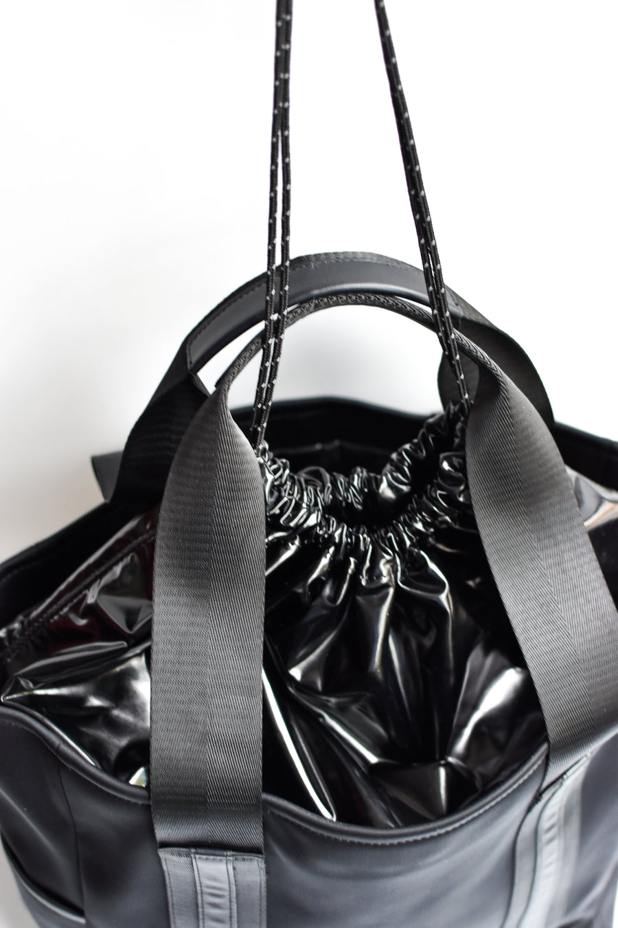 Close up of high shine cinch top on black neoprene tote bag.