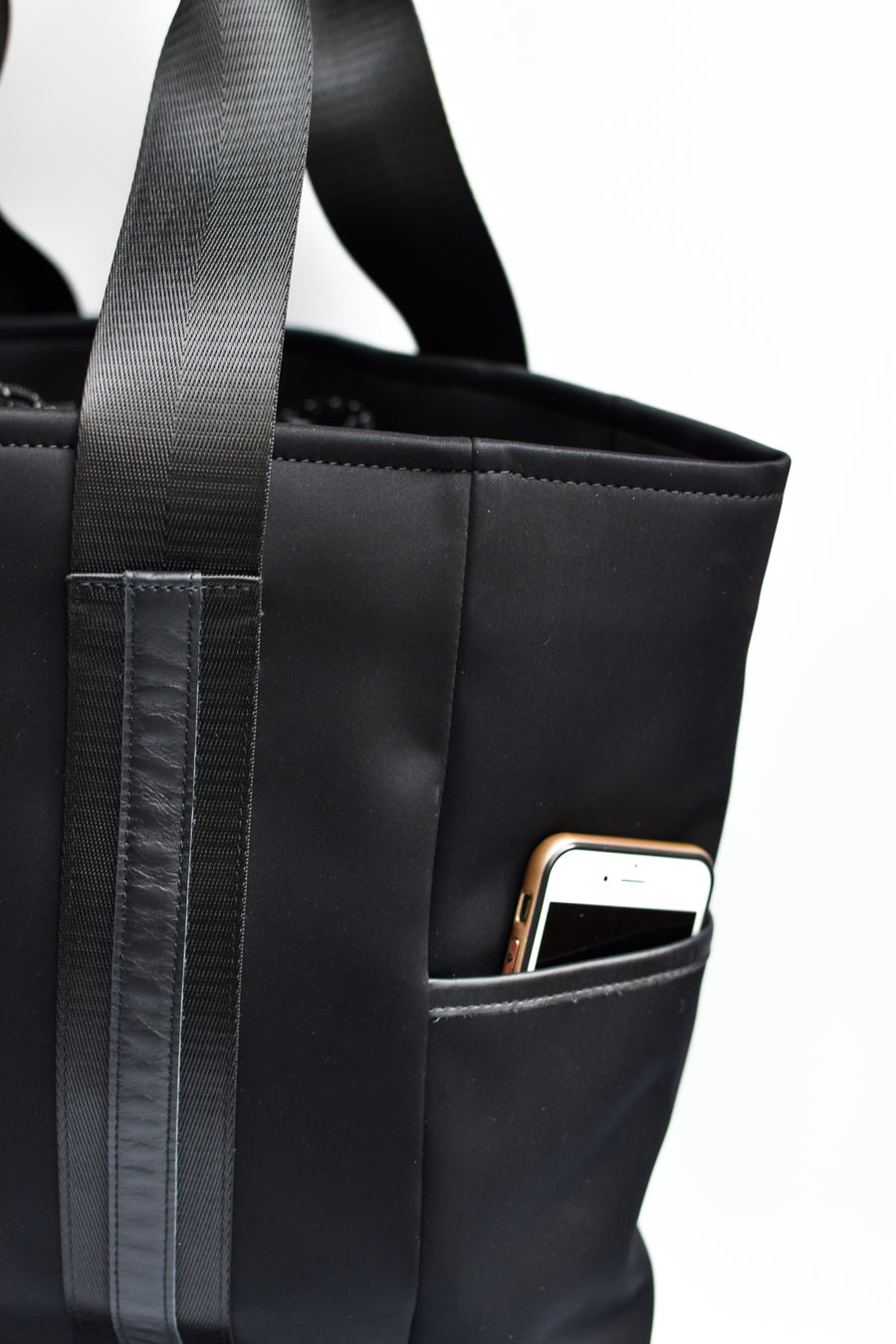 Close up of exterior pocket on black neoprene tote bag with high shine cinch top closure and leather details.