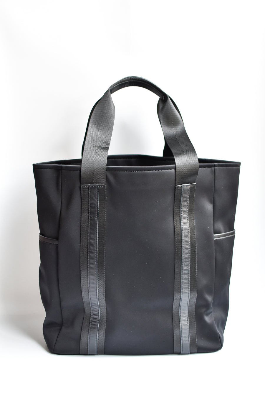 Black neoprene tote bag with high shine cinch top closure and leather details.