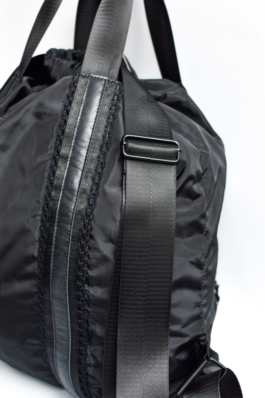 Close up of side detail on black nylon convertible backpack tote with leather details.