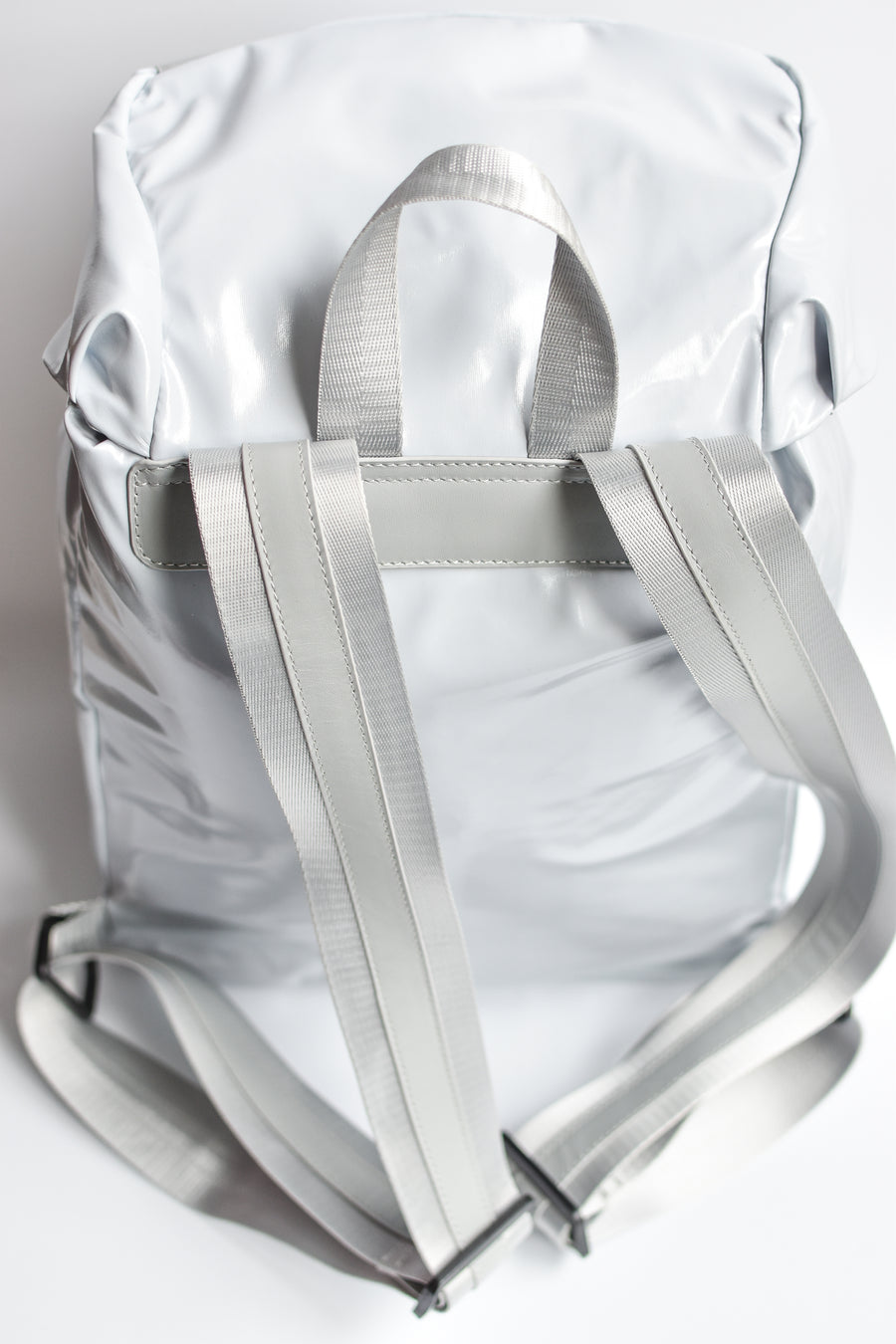 Back view of gray high gloss backpack with gray leather and webbing details.