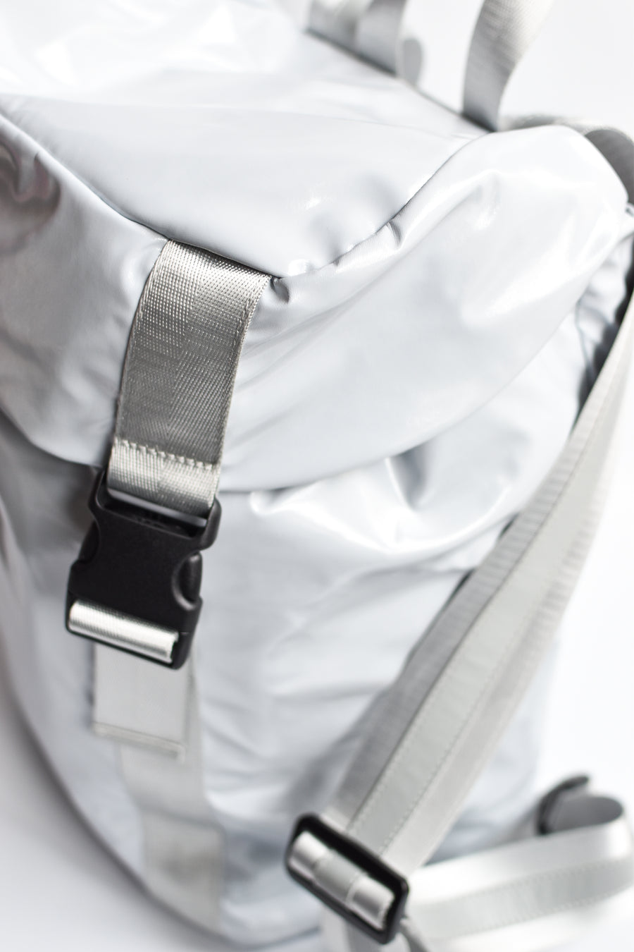 Side view of gray high gloss backpack with gray leather and webbing details.