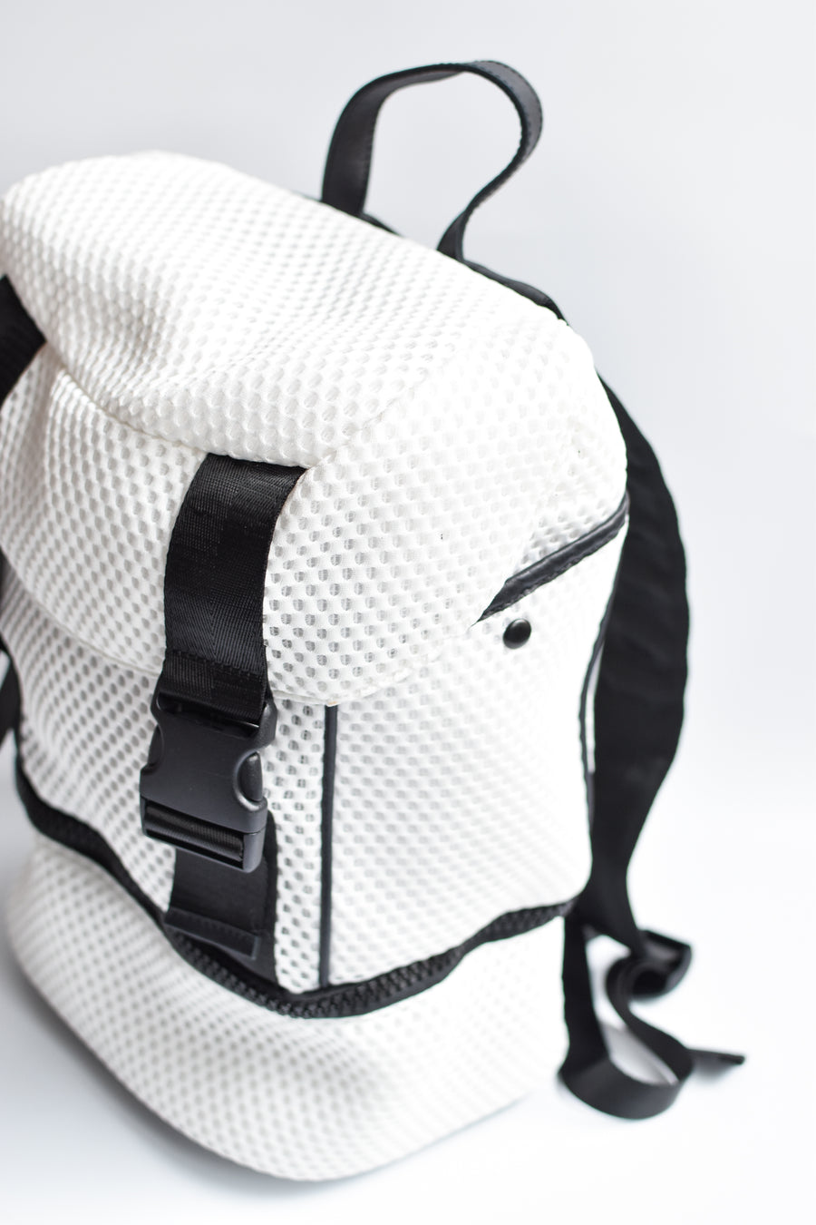 Side view of brooker white mesh backpack with black front straps and bottom zipper compartment with black chunky zipper.
