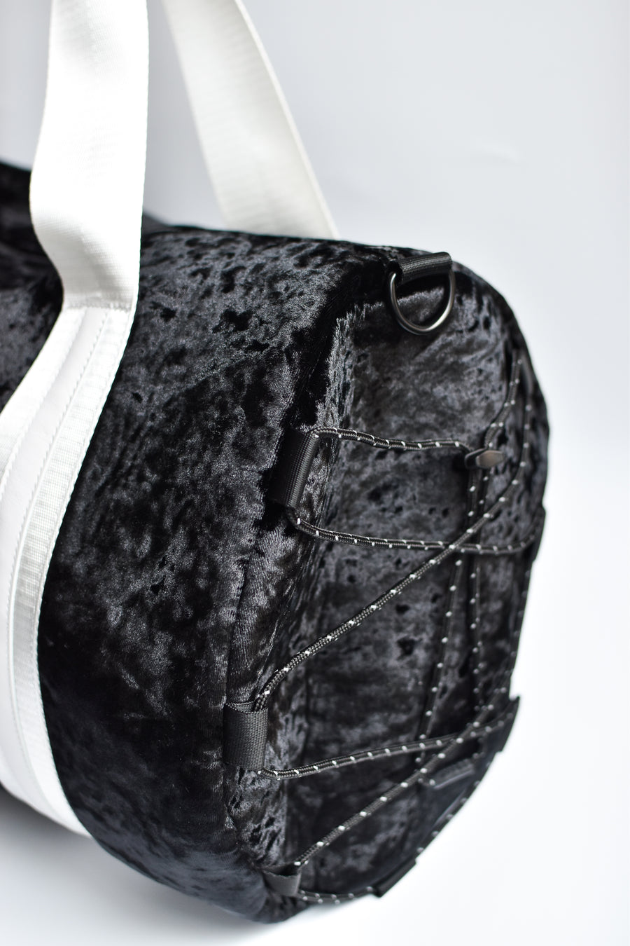 Close up of bungee strap detail on side of black velour duffel bag with white straps and leather details.