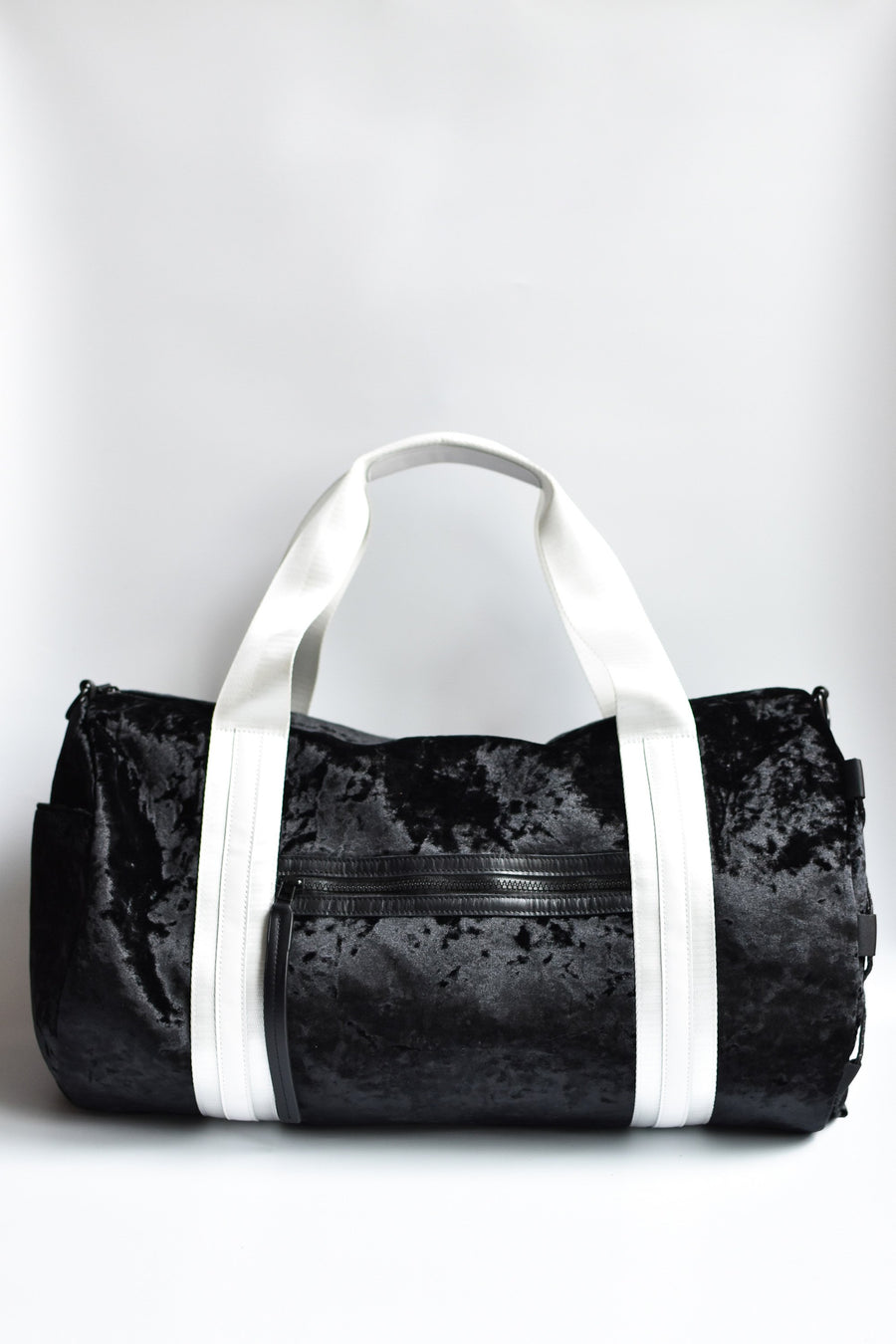 Black velour duffel bag with white straps and leather details.