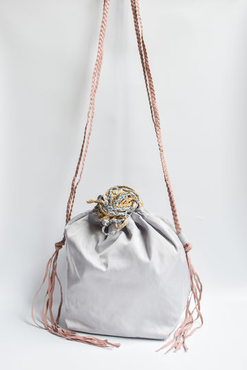 Sporty gray nylon cinch bag with colorful braided leather straps.