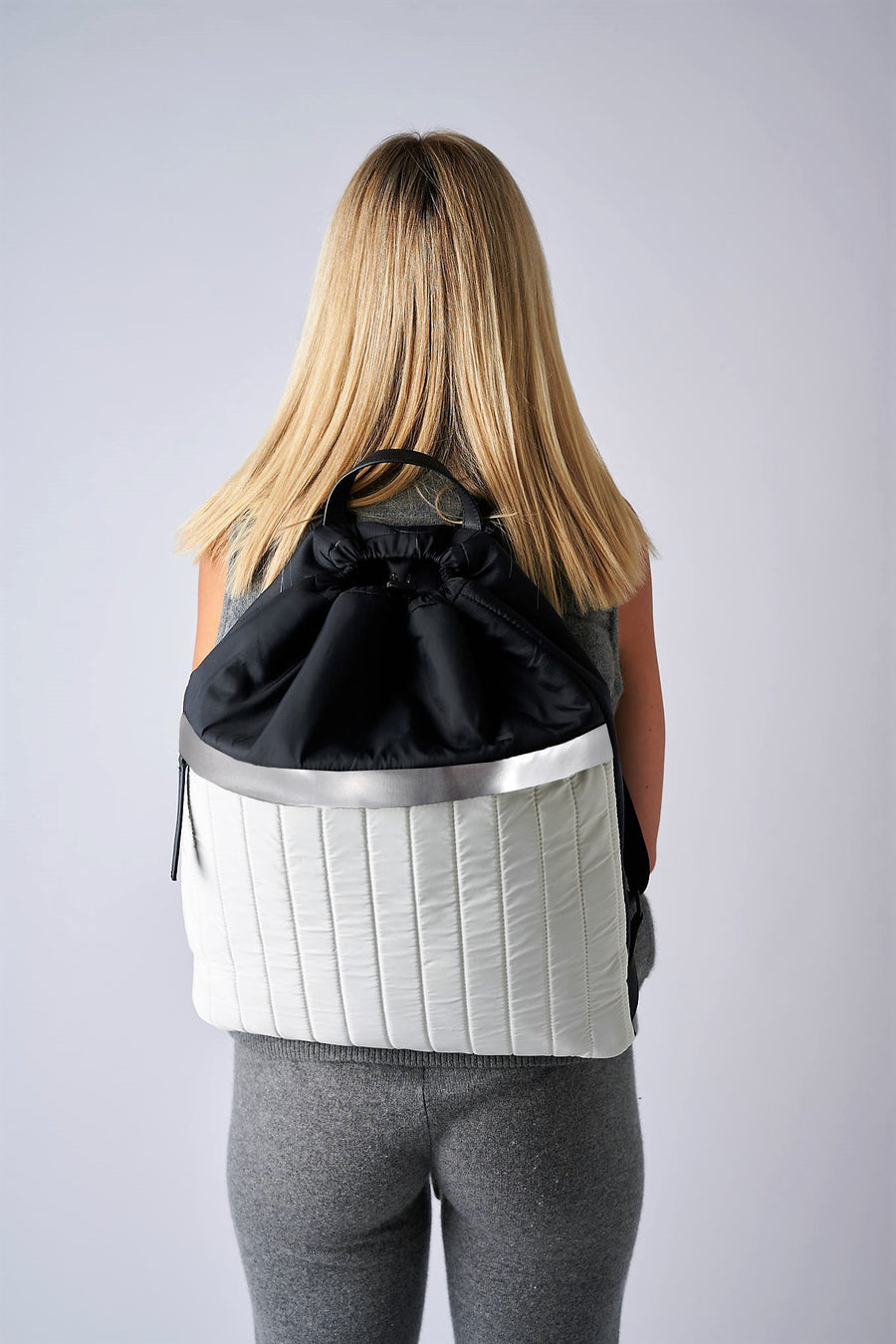 Person wearing black & white nylon cinch top backpack with signature leather and shiny silver details.
