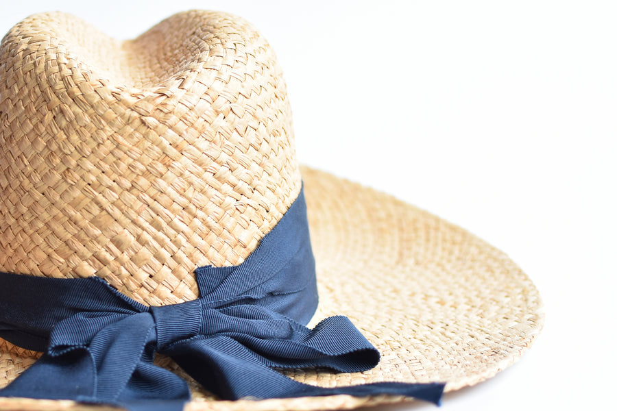 Close up of natural raffia straw panama hat with navy grosgrain tie.