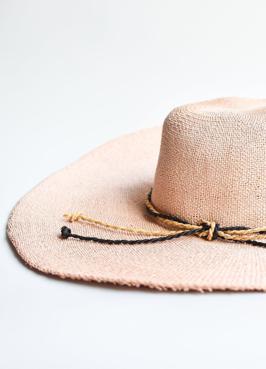 Close up of blush pink floppy straw hat with natural and black braided straw band.