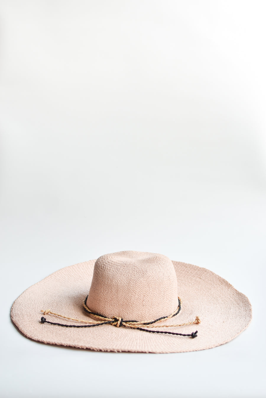 Blush pink floppy straw hat with natural and black braided straw band.