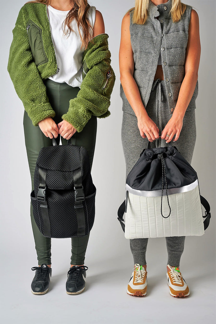 Two people holding Anya & Niki backpacks, including the Newberry black mesh backpack and the Pace black & white nylon cinch top backpack.