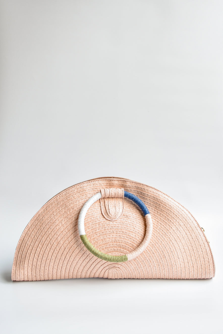 Pink half-moon straw clutch with colorful wrapped circle handle and leather sides.