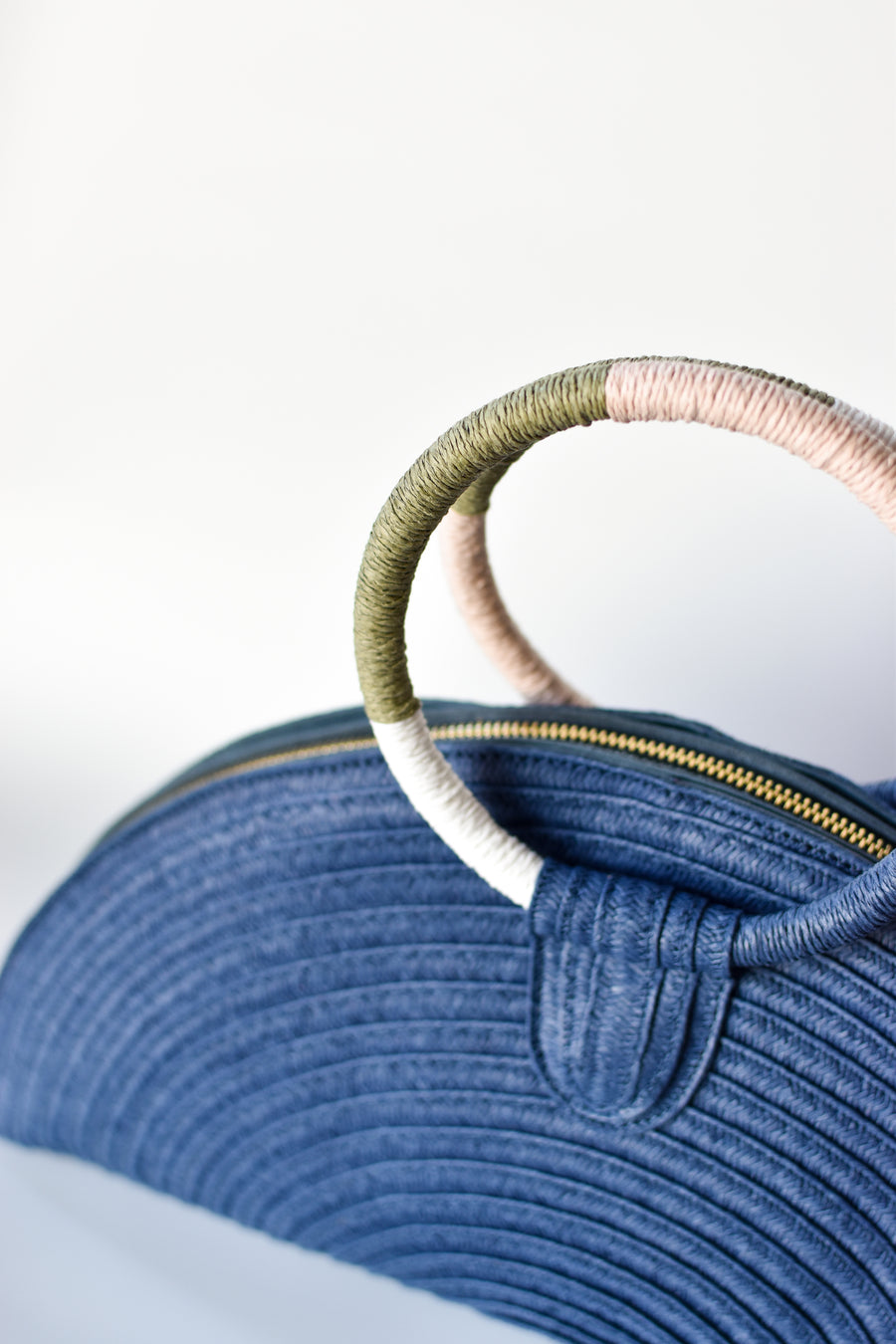 Navy half-moon straw clutch with colorful wrapped circle handle and leather sides..