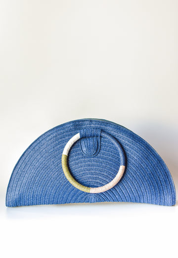Navy half-moon straw clutch with colorful wrapped circle handle and leather sides.