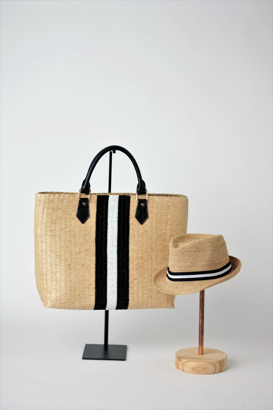 Collection of Anya & Niki Benicia straw tote bag with black leather handles and black & white center stripe, along with the Essential crochet straw hat with black and white band.