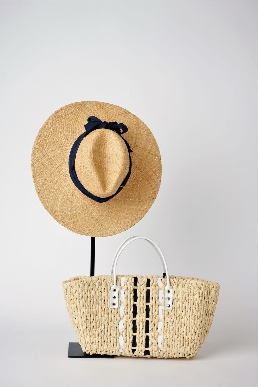 Collection of Anya & Niki straw hat and bag - the Everywhere straw panama hat with black grosgrain band and the Ione petite straw bag with leather details.