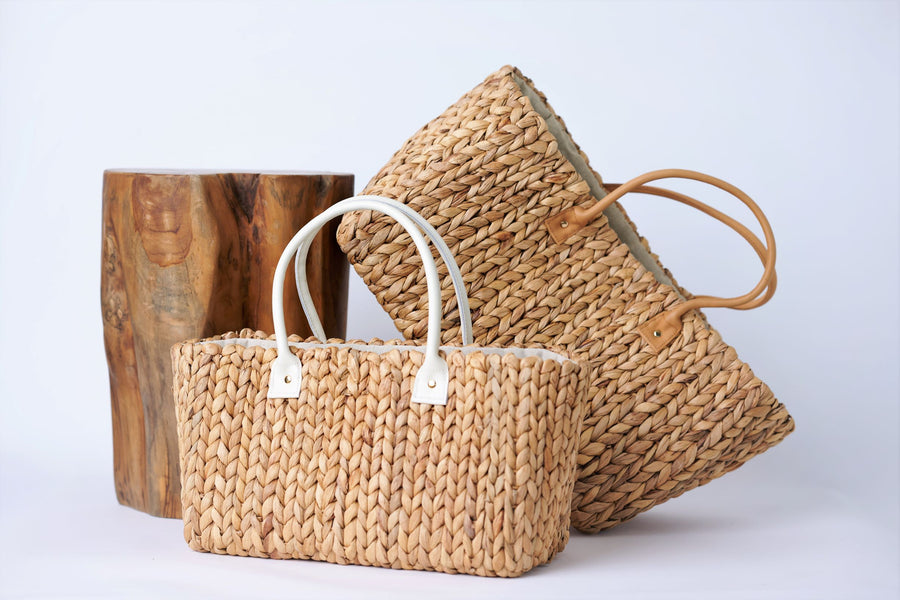 Collection of two Anya & Niki hyacinth straw tote bags with leather handles in a medium and large size.