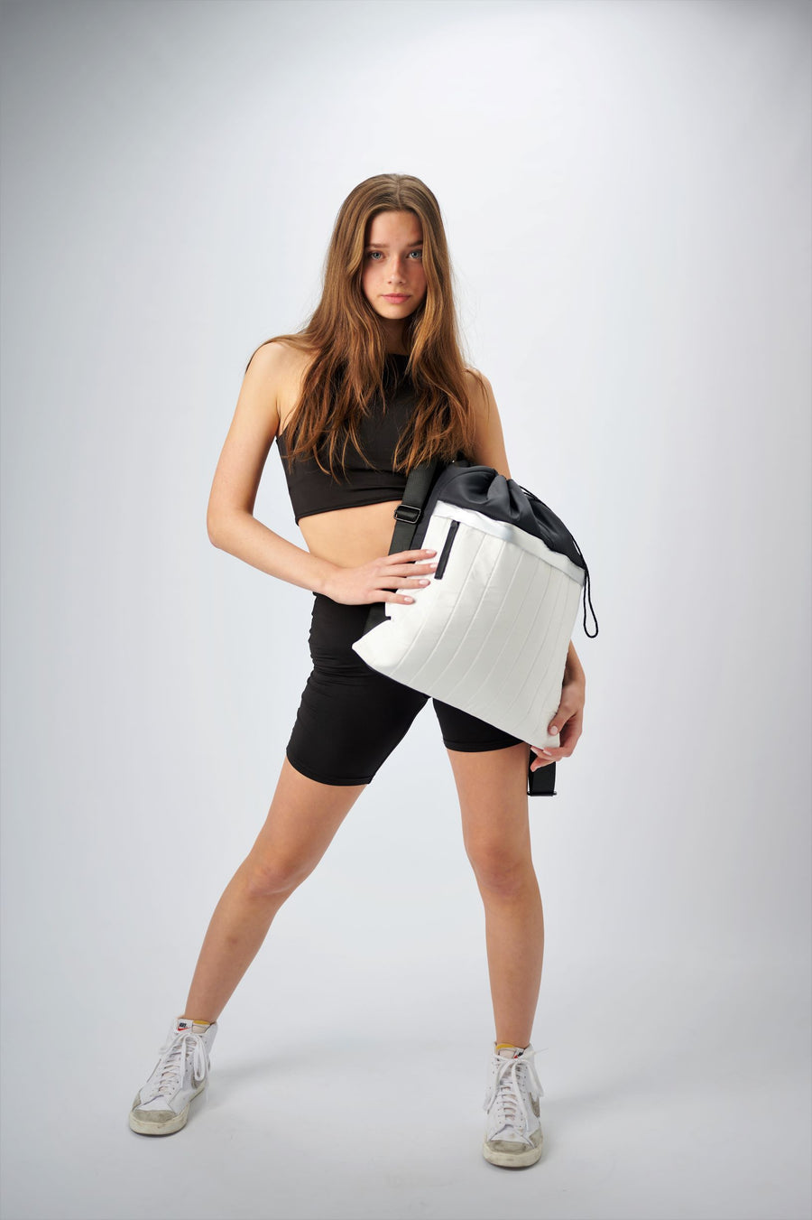 Person holding black & white nylon cinch top backpack with signature leather and shiny silver details.