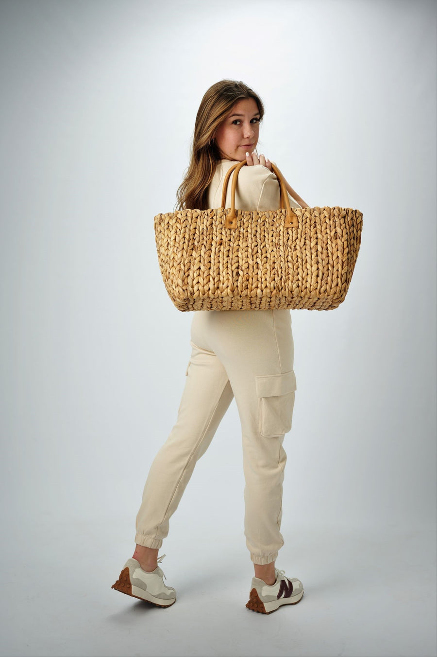 Person holding the Fullerton Straw Tote - a large natural hyacinth straw tote with matching leather handles.