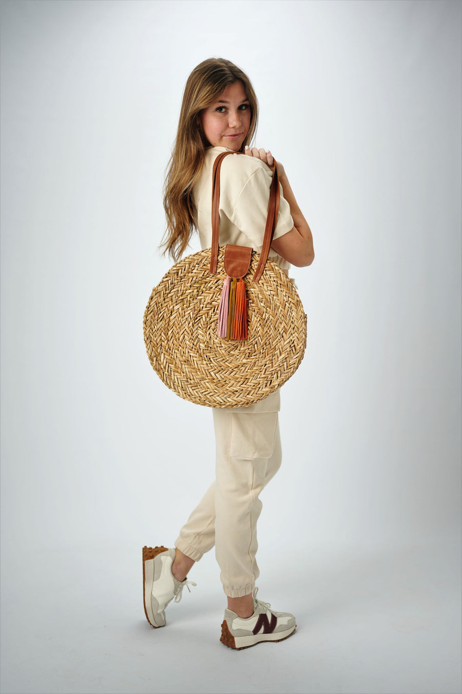 Person holding the Palmdale Straw Bag - a natural seagrass round straw bag with leather handles and suede tassel closure.