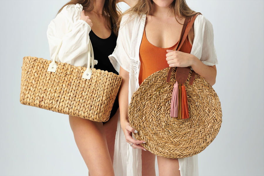 Two people holding Anya & Niki straw bags,  the Augustine hyacinth midsized straw tote with leather handles and the Palmdale circle straw tote with suede tassel detail and leather handles.