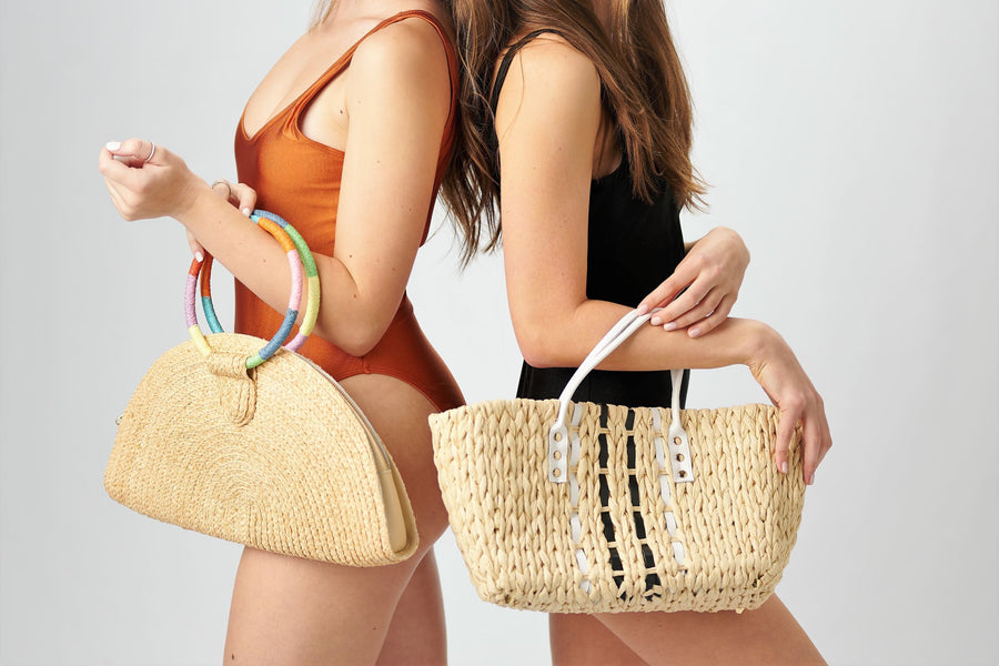 Two people holding Anya & Niki petite straw bags - the Palma halfmoon straw clutch and the Ione straw bag with leather handles.