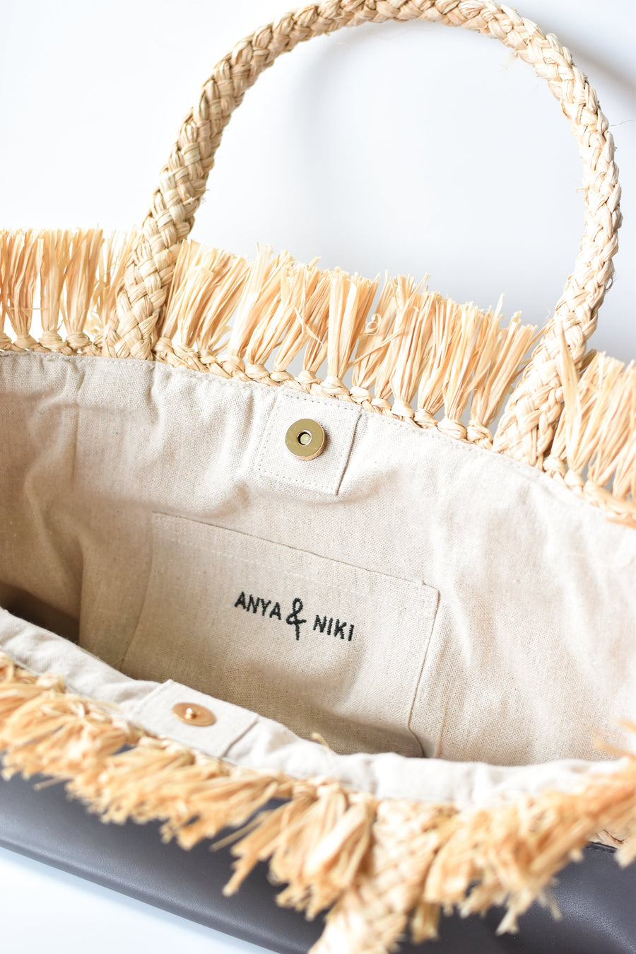 Close up of interior linen lining on natural raffia straw tote with gray color block base.