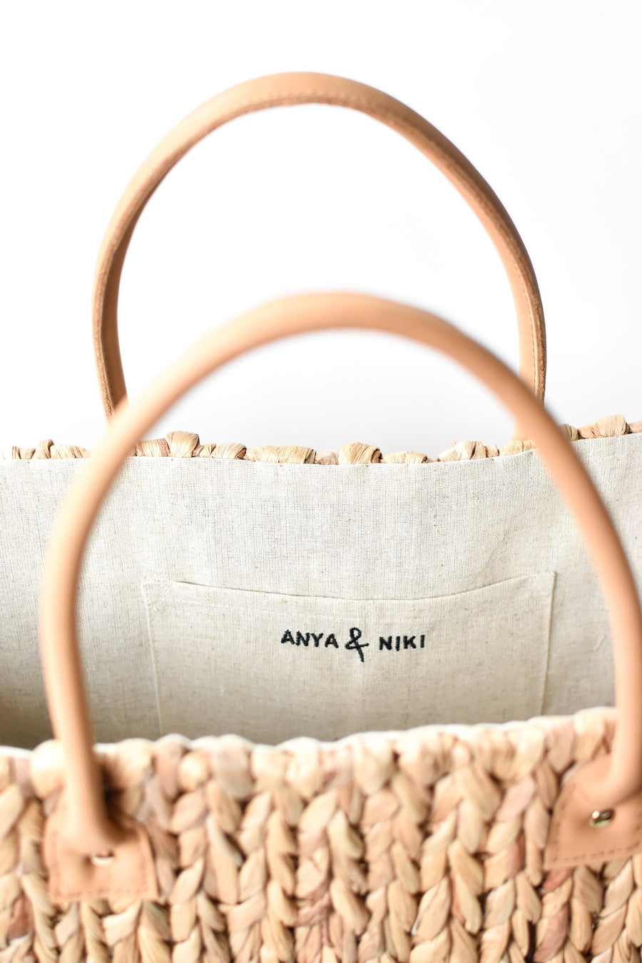 Close up of tan leather handles on large natural hyacinth straw tote.