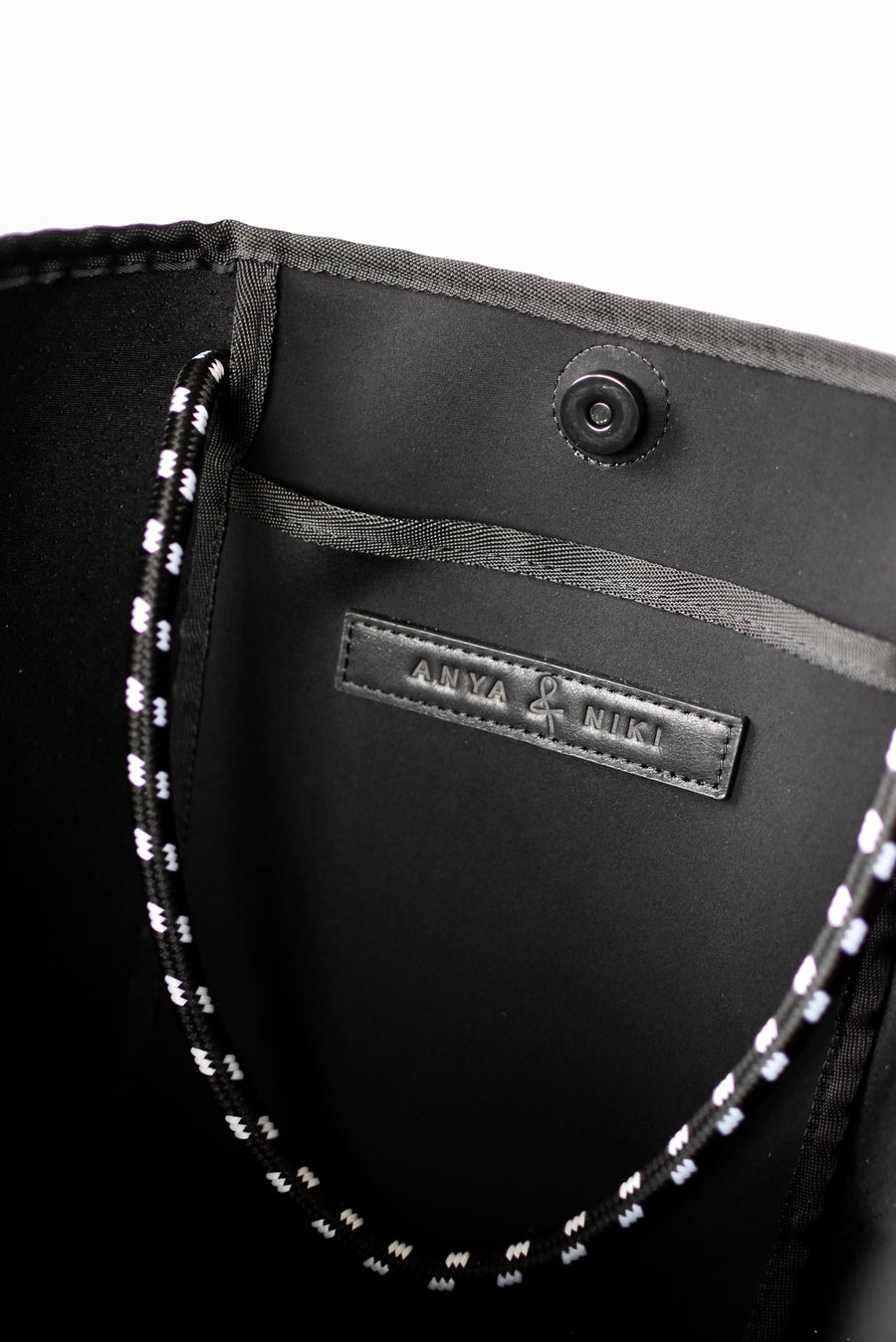 Close up of interior pocket on gray perforated neoprene tote bag.