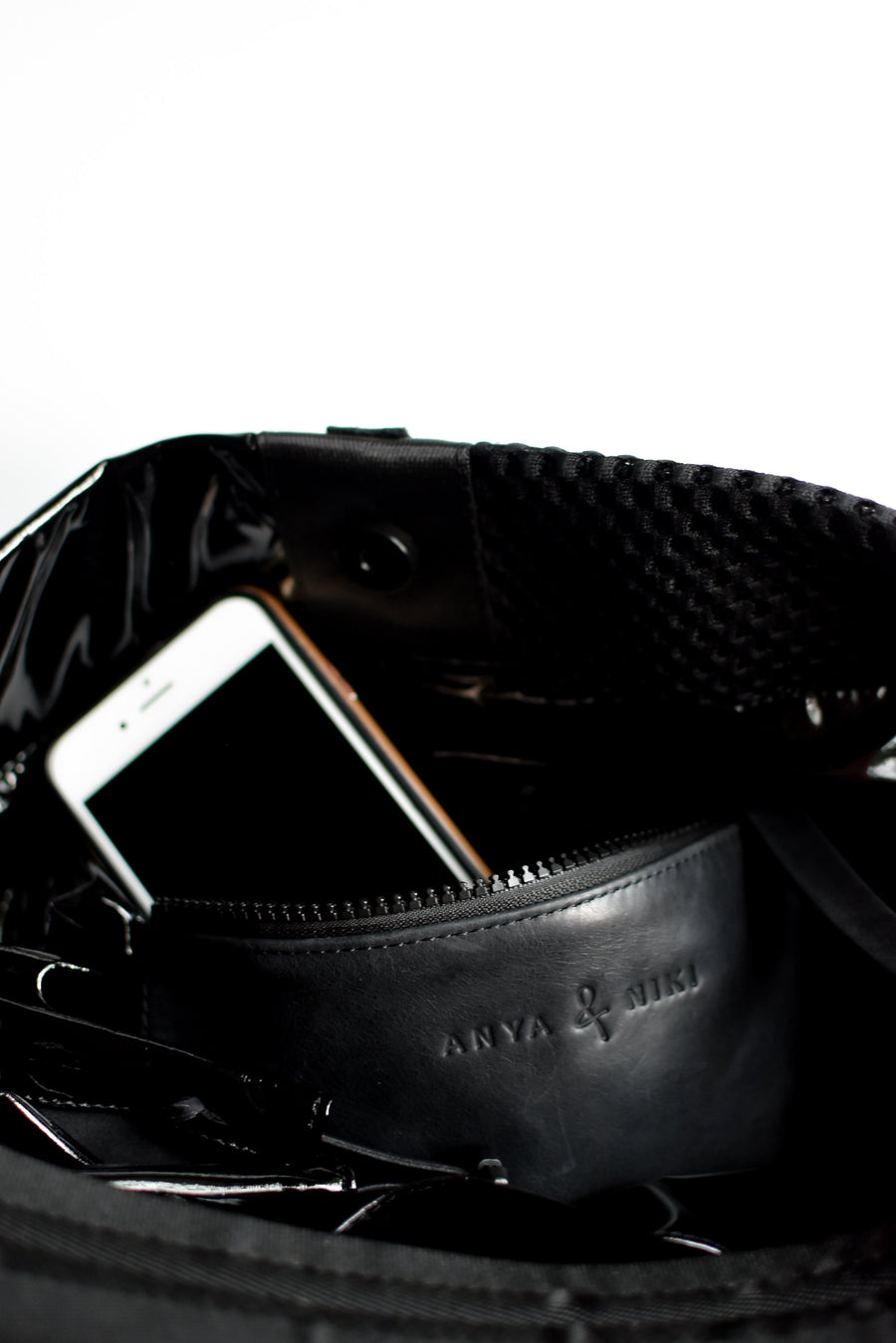 Close up of interior leather pocket on black sporty mesh and shiny vinyl tote bag.