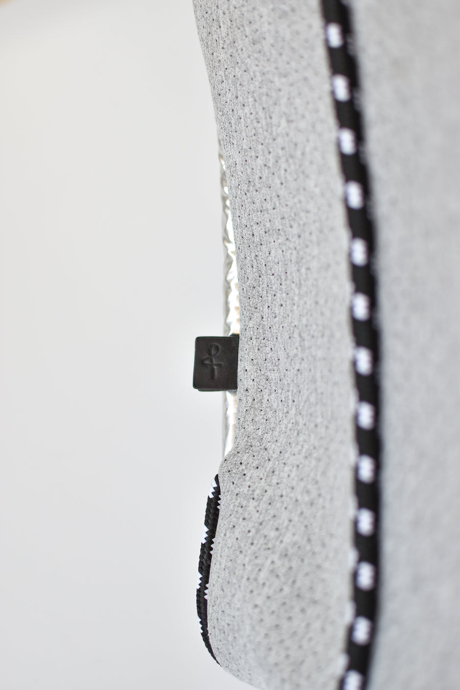 Close up of leather logo tab and cording detail on perforated gray neoprene tote bag.
