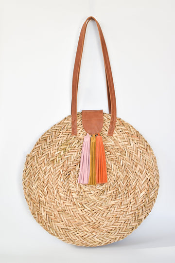 Natural seagrass round straw bag with leather handles and suede tassel closure.