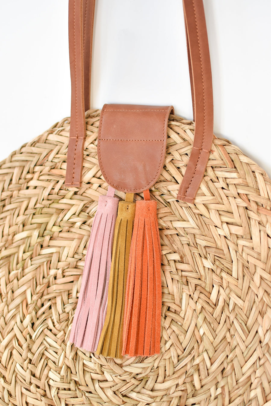Close up of natural seagrass round straw bag with leather handles and suede tassel closure.