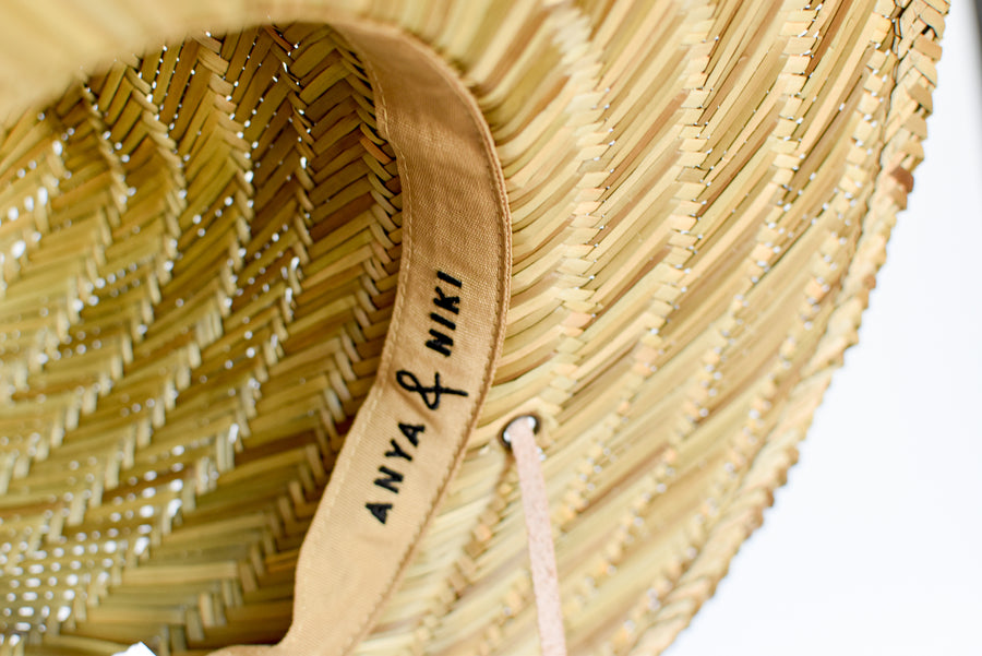 Close up of adjustable interior band on straw lifeguard hat.