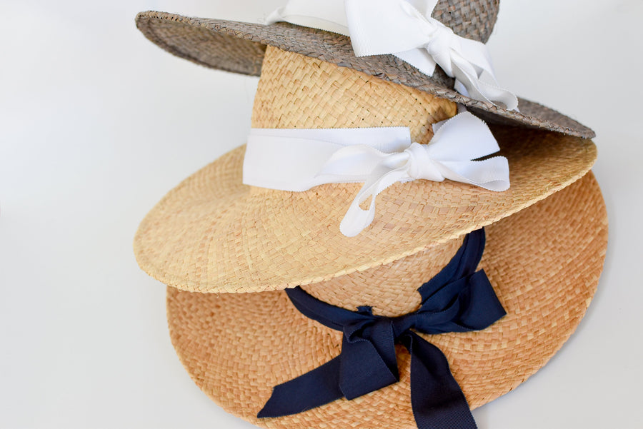 Stacked collection of raffia straw panama hat with grosgrain ties from Anya & Niki. Natural straw with white or navy bands or gray straw with white band.