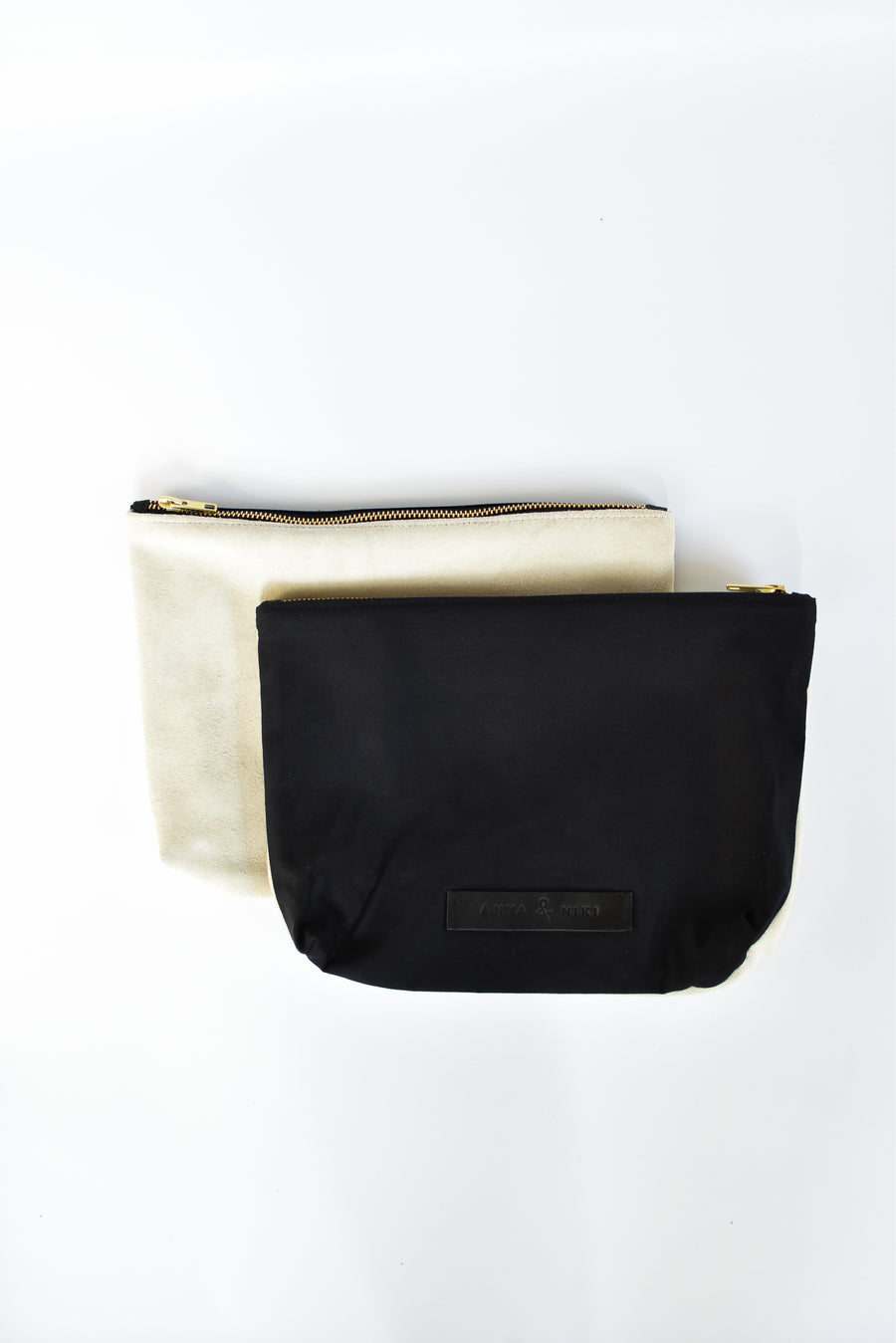 Black cotton canvas and off-white suede medium pouch with brass zipper and leather logo label.