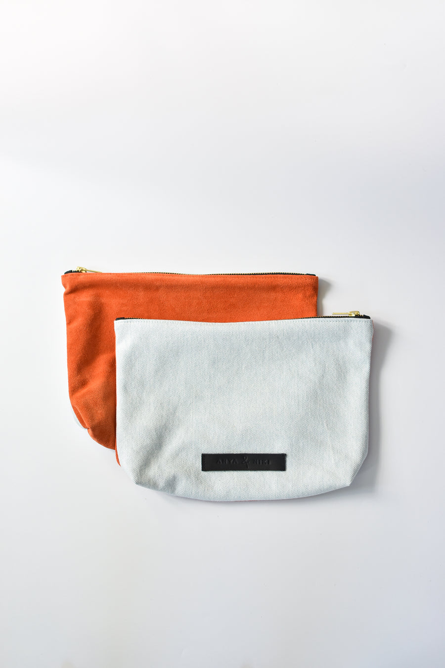 Washed denim and orange suede medium sized pouch with brass zipper and leather logo label.