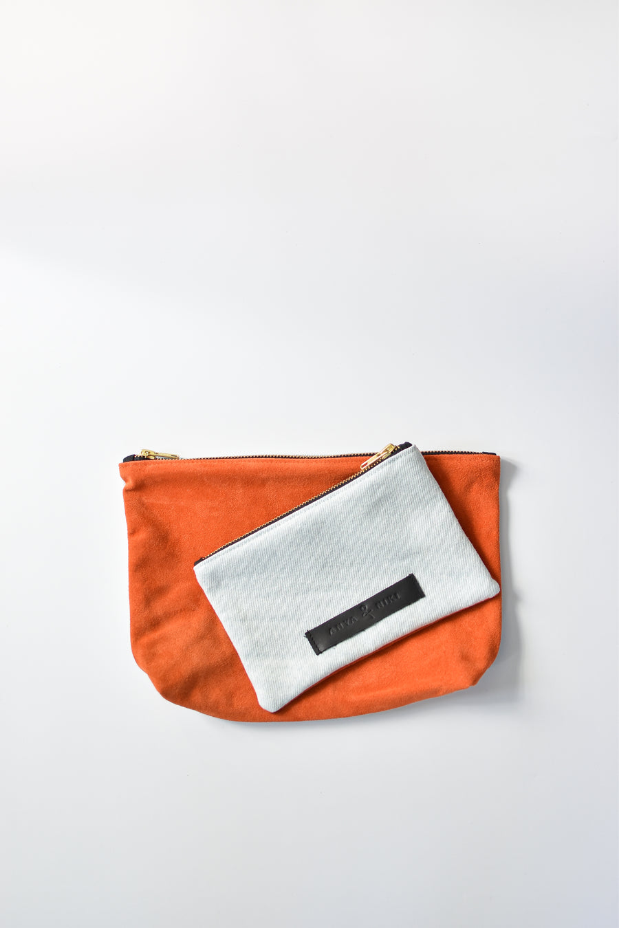Washed denim and orange suede medium and small pouch with brass zipper and leather logo label.