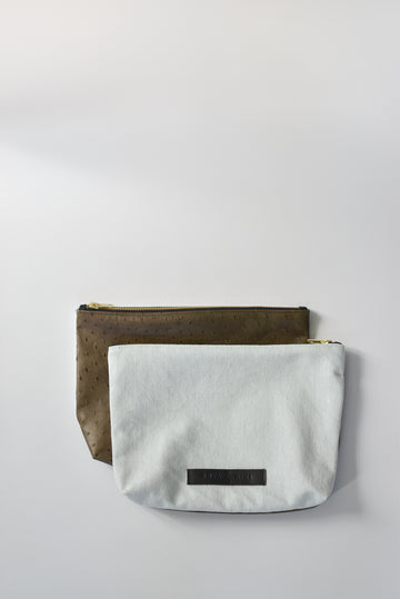 Bleached denim and fern colored embossed leather skin medium pouch with brass zipper and leather logo label.