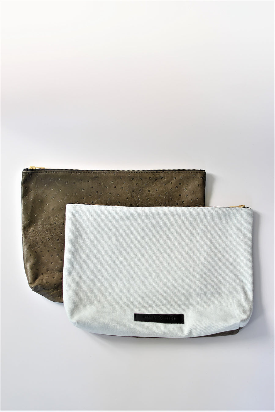 Bleached denim and fern colored embossed leather skin large pouch with brass zipper and leather logo label.