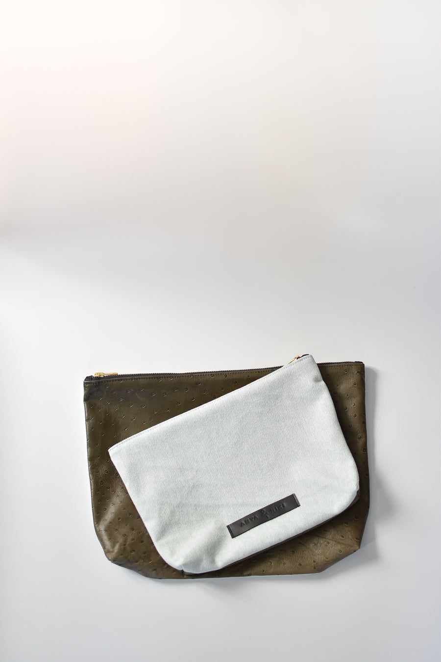 Bleached denim and fern colored embossed leather skin medium and large pouch with brass zipper and leather logo label.