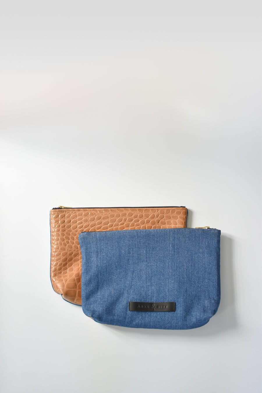 Medium wash denim and caramel colored embossed leather skin medium pouch with brass zipper and leather logo label.