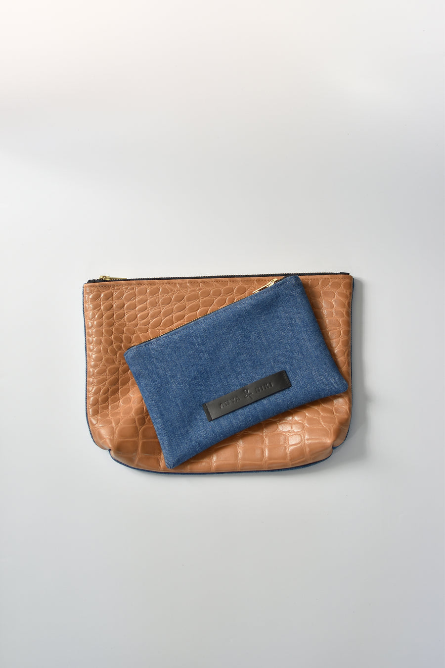 Medium wash denim and caramel colored embossed leather skin small and medium pouch with brass zipper and leather logo label.